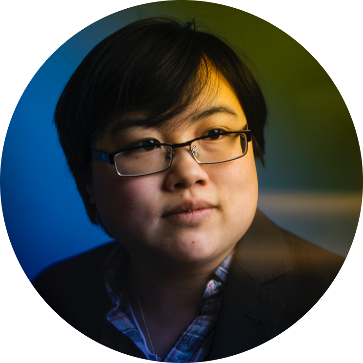 [Photo: Headshot of Lydia Brown, young East Asian person, with short black hair, wearing glasses, a plaid shirt, and black jacket. They are looking in the distance, posed against a stylized blue and yellow dramatic background. Photo by Adam Glanzman.]
